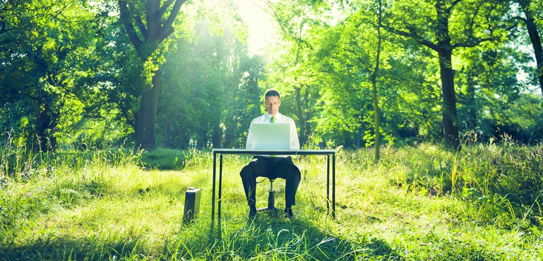 man sitting at a desk in the forest