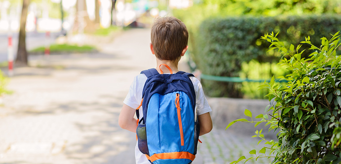 Child walking with backpack