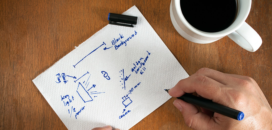 Man drawing on paper while having morning coffee