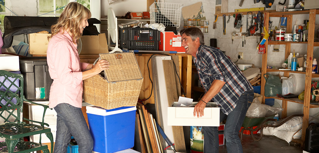 Man and woman happily browsing through boxes in garage
