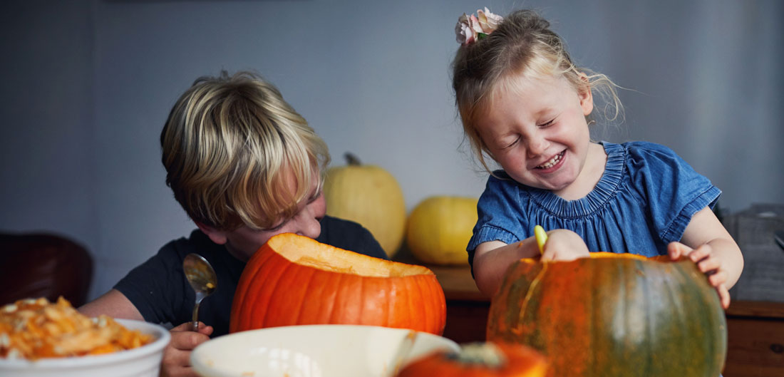 two children giggle and carve pumpkins