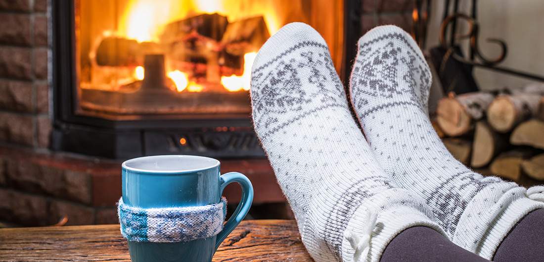 cozy socked feet by a fireplace