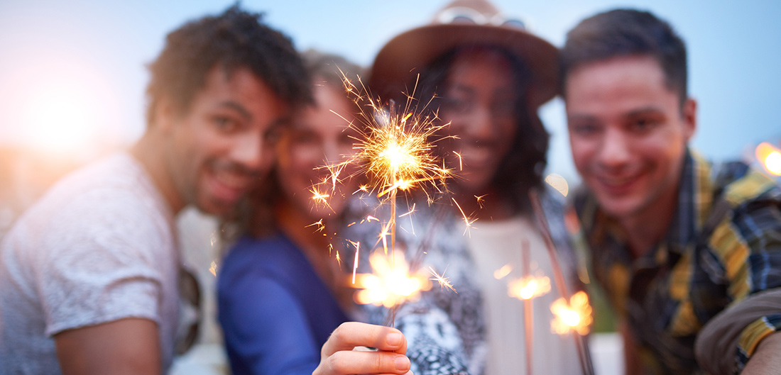 4 people playing with sparklers
