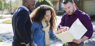 couple looks at paperwork with agent