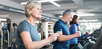 senior woman runs on treadmill at gym