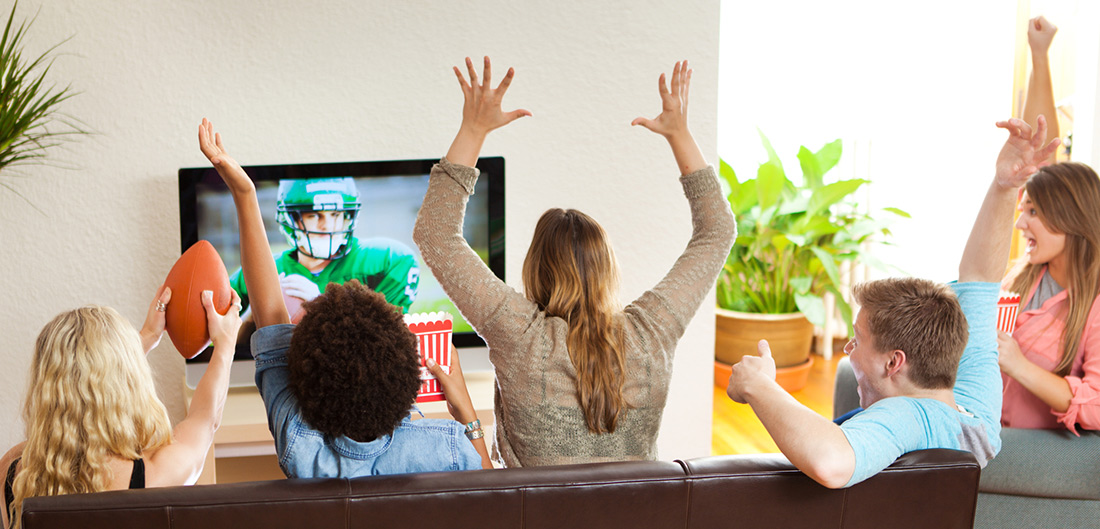 people cheering in living room watching football game