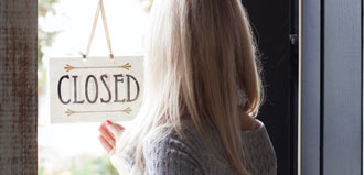 woman flips open closed sign on business door
