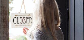 woman flips open closed sign on business door