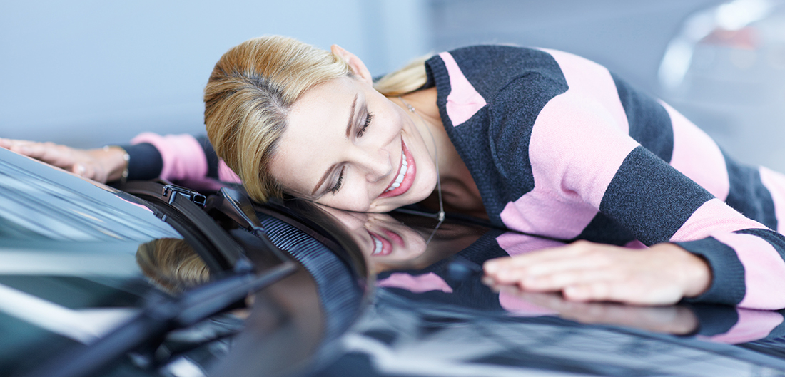 woman laying on blue car and smiling