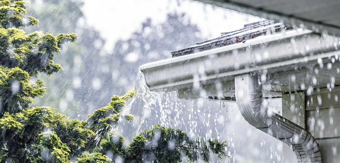 rain pours onto gutters on home