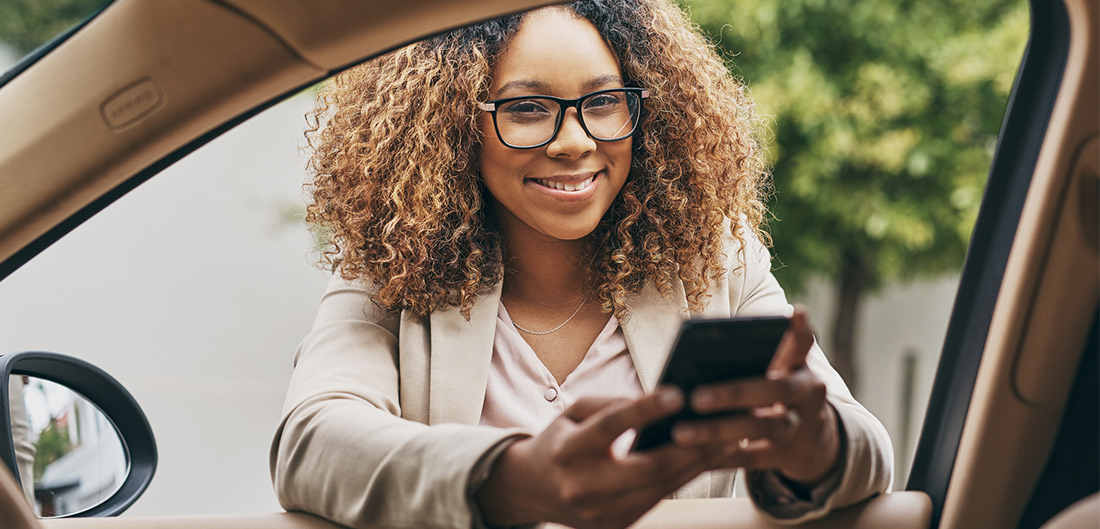 business woman standing outside of company car with mobile phone