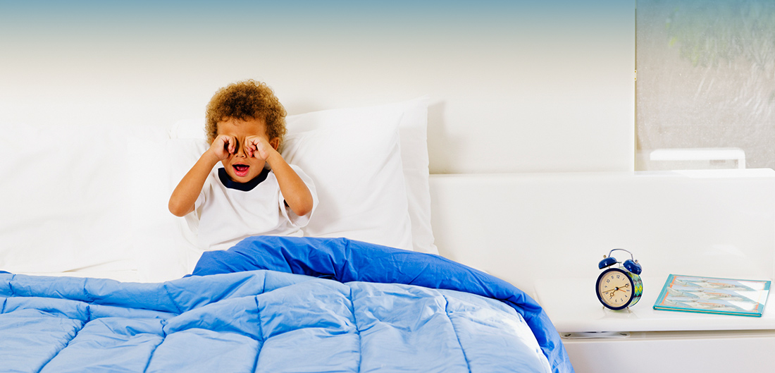 little boy rubbing his eyes in bed with a clock next to him