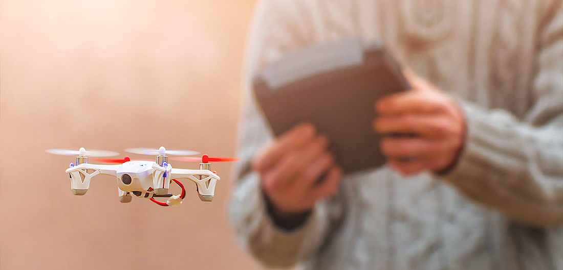 man in sweater flies drone