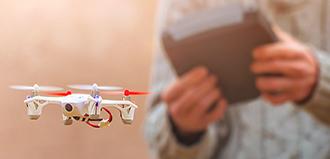 man in sweater flies drone