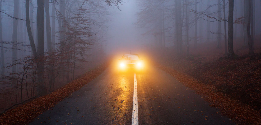 headlights from car on foggy street