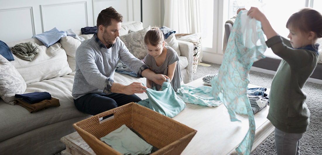 stay at home dad folding laundry with kids