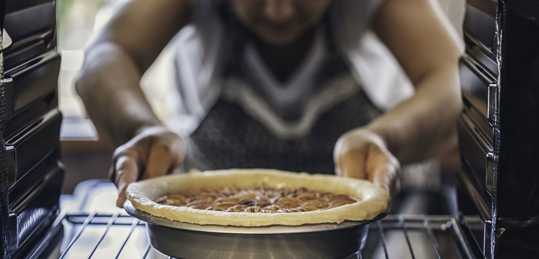 woman places pecan pie in oven