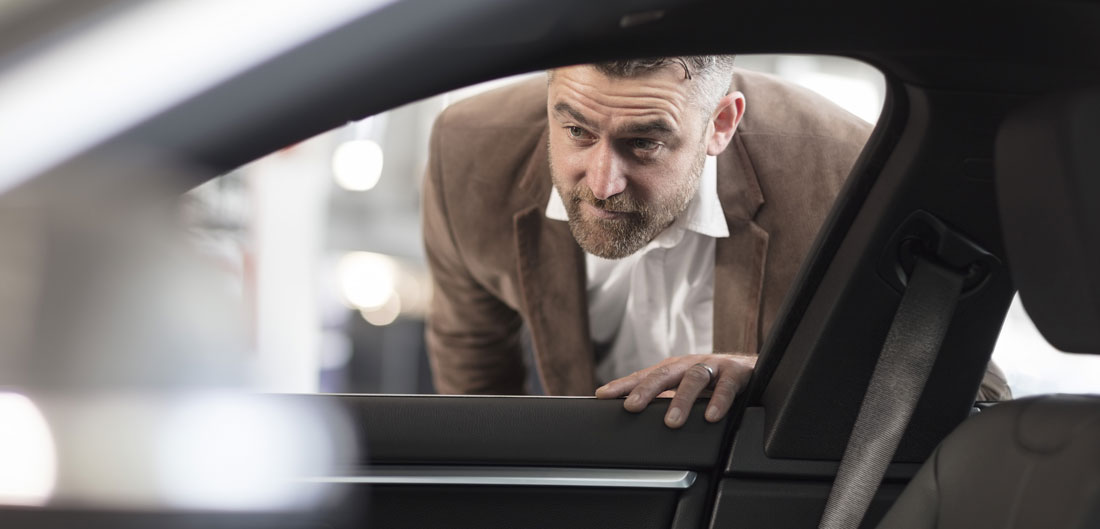 man looks in window of new car at dealership