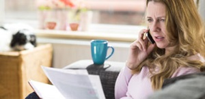 upset woman looks at bill while talking on phone