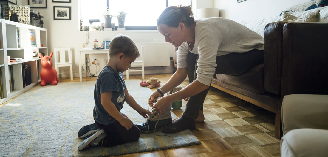 mom helps child tie shoelaces