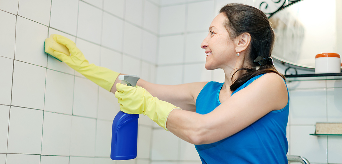 woman scrubbing bathroom shower tiles