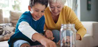 grandson and grandmother put coins in jar