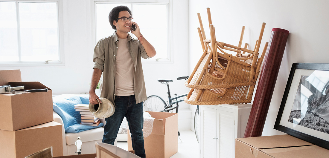 Young African American Male On Phone Unng Moving Boxes In Apartment