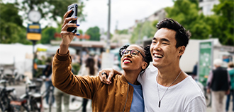 Two millennials laughing and smiling while taking a selfie