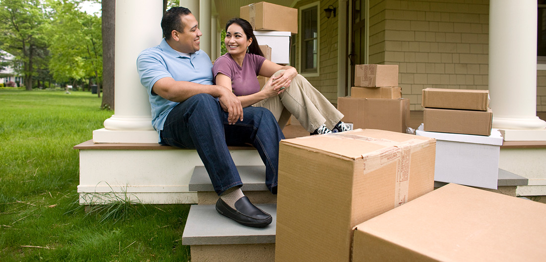 man and woman sitting on the front porch of a house with moving boxes surrounding them