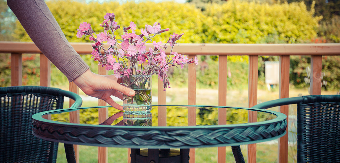 woman adding flowers to outdoor table
