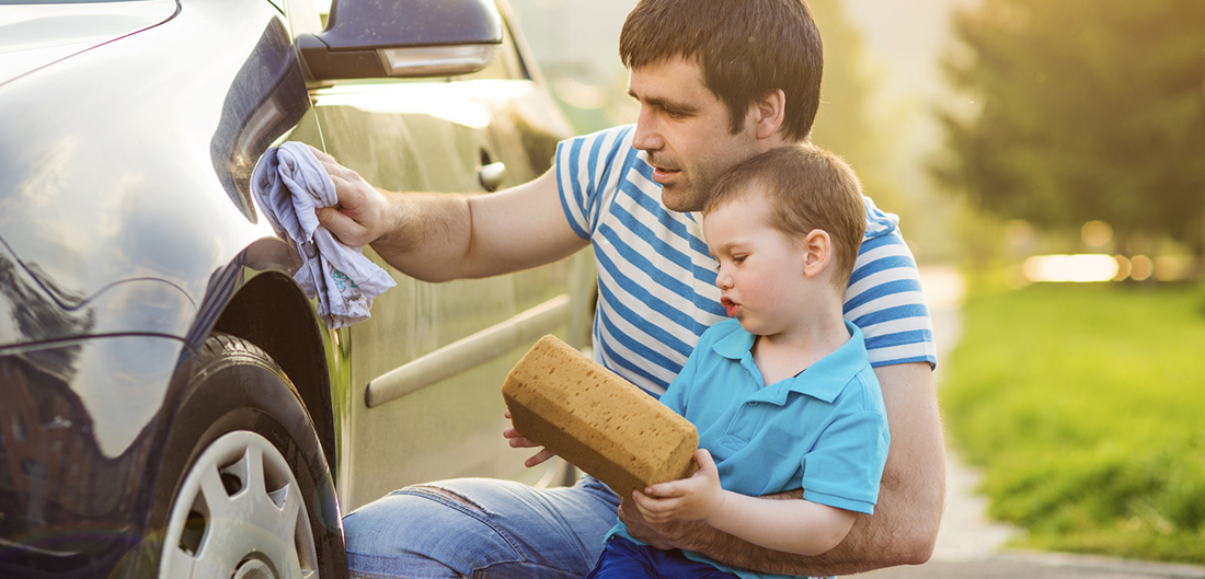 dad and son washing car in the spring