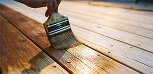 person using paintbrush to stain wooden deck