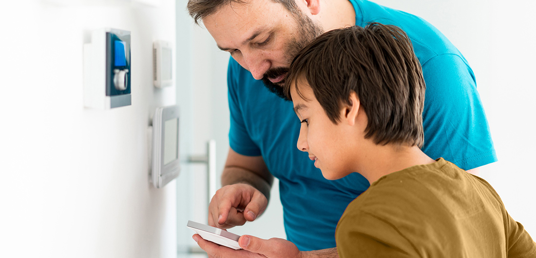 father and son checking their smart home smoke alarm