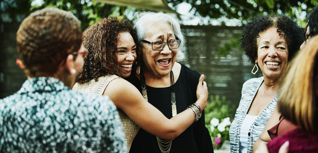 young adult woman hugs senior woman at family gathering