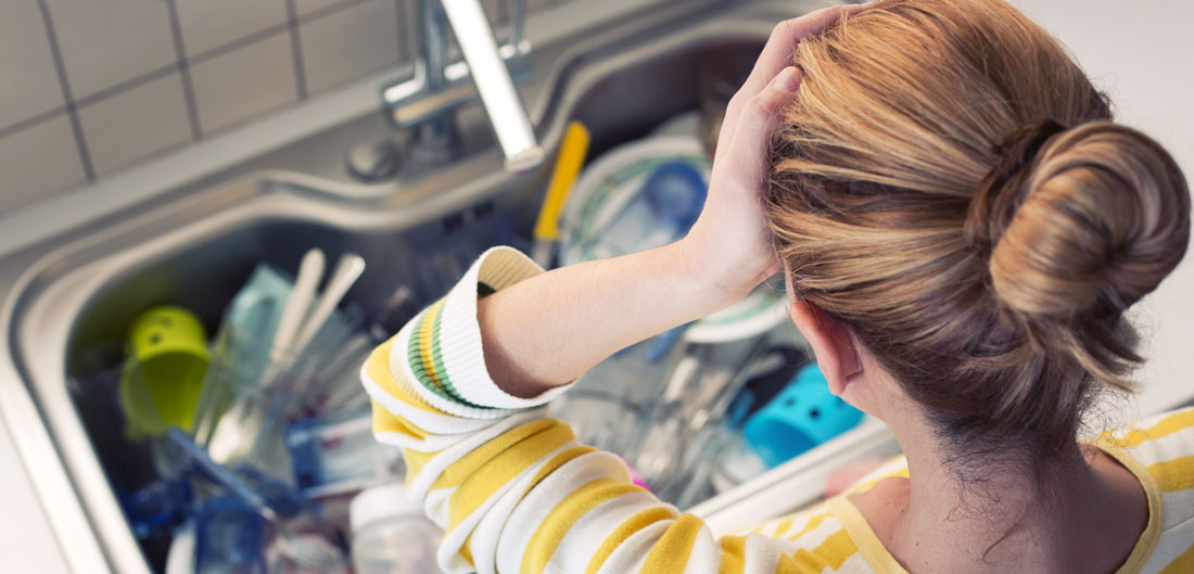 woman looks upset at sink full of dishes