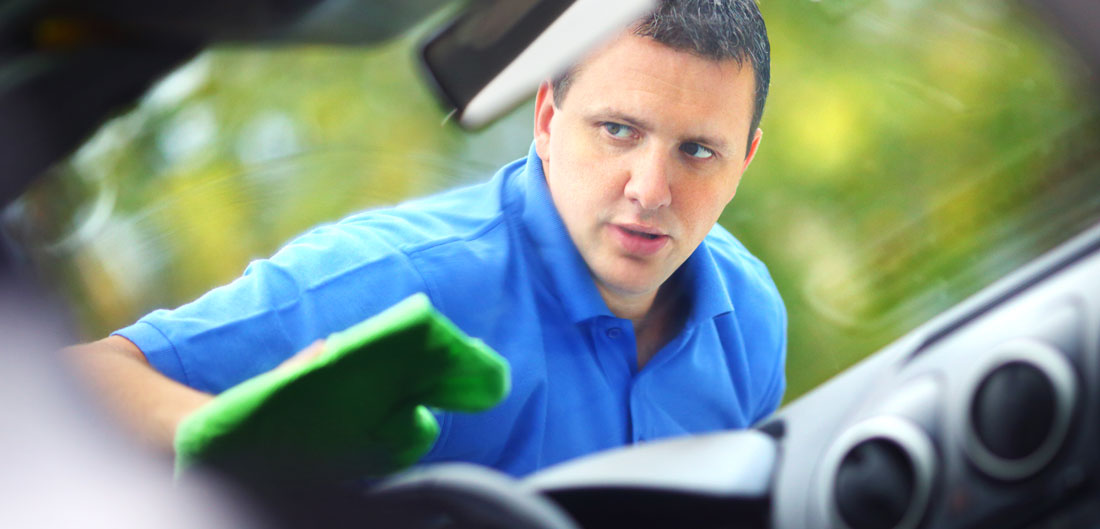 man wipes car windshield suspiciously