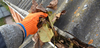gloved hand cleans leaves out of gutter