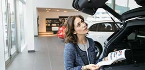 woman examines car in showroom