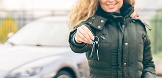 woman in winter coat holds car keys