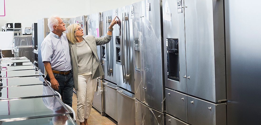 senior couple looks at new refrigerators in appliance store