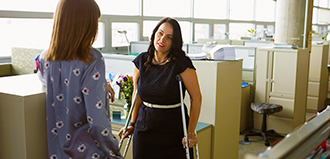 woman on crutches talks to woman coworker at cubicles