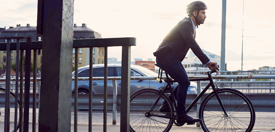 man in suit rides bicycle through urban landscape
