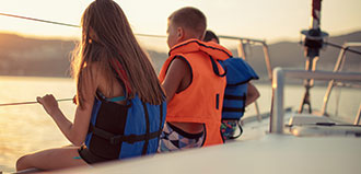 two children, girl and boy, wear life jackets on deck of boat looking at sunset