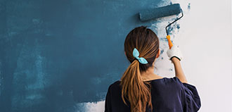 woman paints wall with paint roller