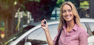 young woman smiles and holds car keys outside driver