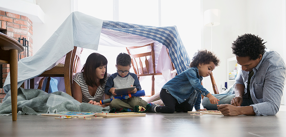 Mom, Dad, and two young children play on floor beneath blanket fort