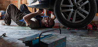 man lies down working on underside of car