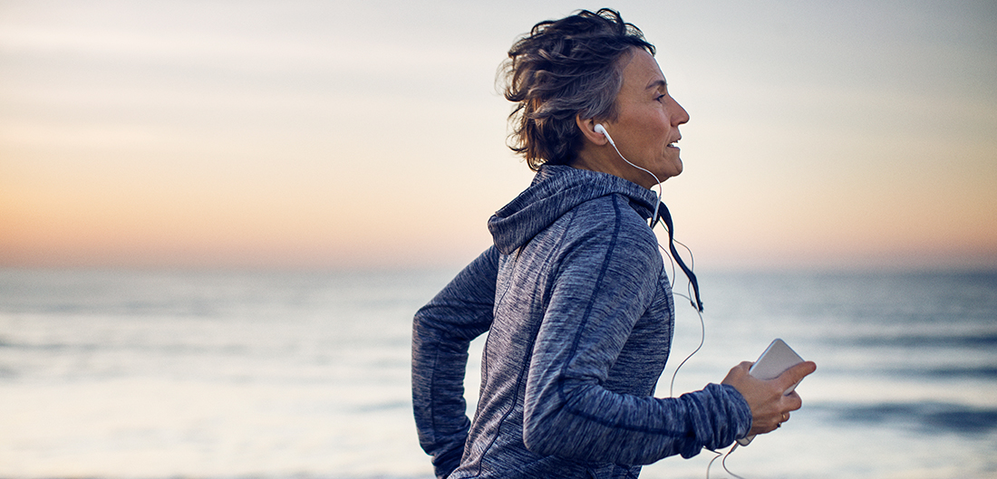 middle aged woman listens to headphones while she runs on the beach at sunset