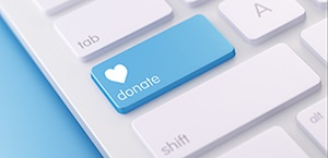 concept image of donate button on computer keyboard