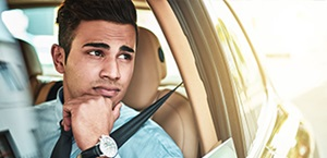 young man gazes distractedly out driver's side window of car